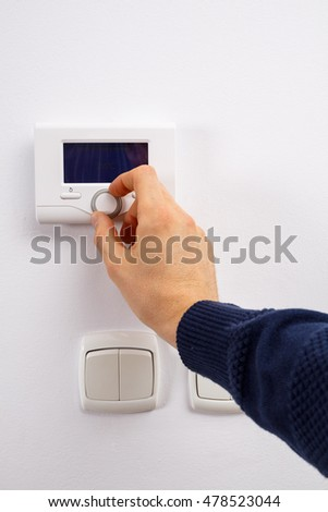 Men hand setting the temperature on control panel of DHW or central heating.