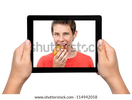 Men hands hold a tablet touch pad computer gadget with a boy and a red apple on the screen - stock photo