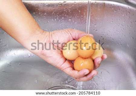 Men Hands Washing Eggs At The Sink - stock photo