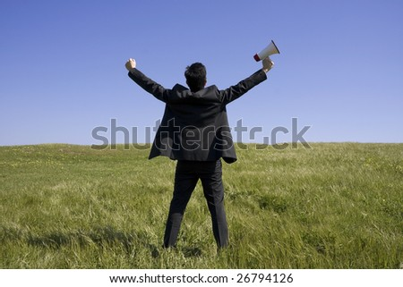 Men holding a megaphone Businessman with his arms outstretched on a field with a blue sky - stock photo