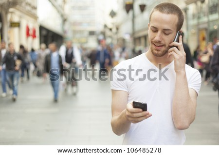 Men holding in hands two mobile phone, city street and people in background - stock photo