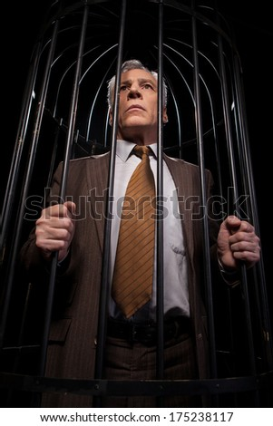 Men in cell. Low angle view of rustrated senior man in formalwear standing in cell and looking away while isolated on black background