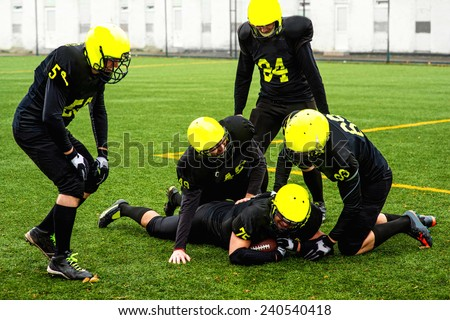 Men in green sportswear and helmet playing american football on the sports ground - stock photo