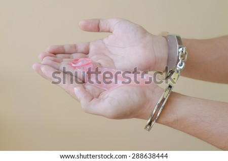 Men in handcuffs holding condom in hand - stock photo