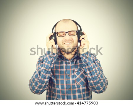 Men in headphones listens to music and sings. Isolated on a gray background. - stock photo