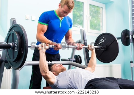 Men in sport gym training with barbell for fitness - stock photo