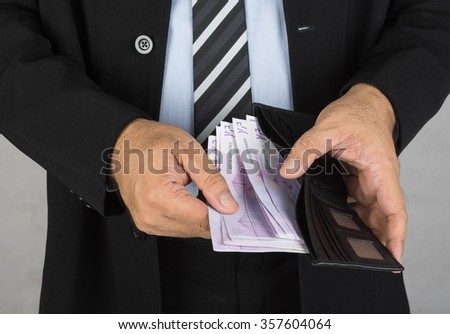 Men in suits are taking money out of the wallet - stock photo