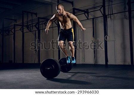 Men jumping over barbells during burpees exercise - stock photo
