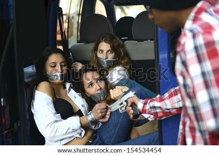 Men kidnapping gagged and tied up women - stock photo