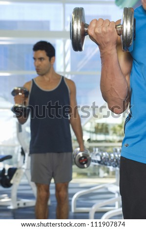 Men lifting weights at a gym - stock photo