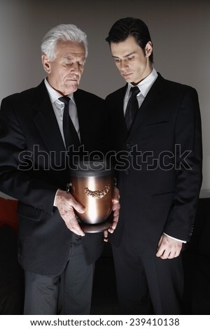 Men Looking at Funeral Urn - stock photo