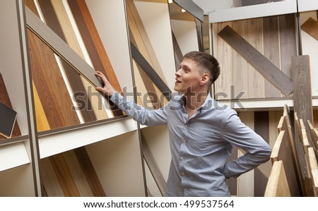 Men looking at parquet board for home flooring in store, in home improvement warehouse exterior