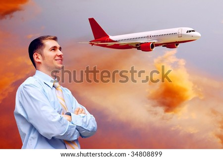 men looks at airplane in air with sunrise sky - stock photo