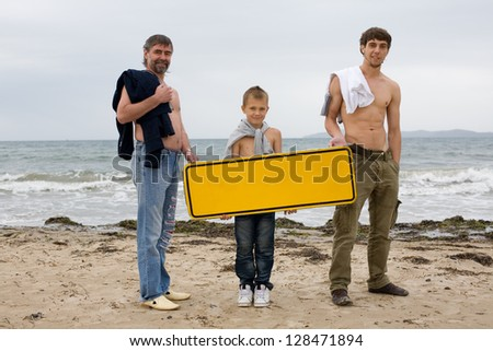 Men of different generations hold an empty banner on the beach.
