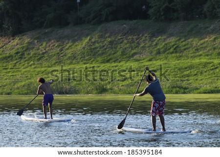 Men paddleboarding at sunset, Florence river, Italy, recreation sport paddling ocean beach surf - stock photo