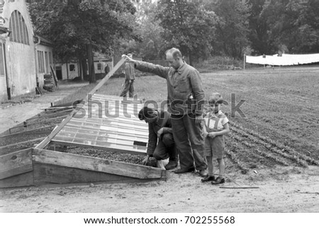 Men planting seeds in small greenhouse on farm