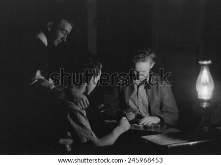 Men play cards by the light of a kerosene lantern. Pie Town, Mexico, 1939.