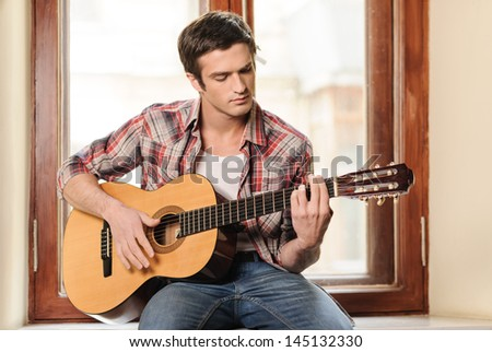 Men playing guitar. Handsome young men sitting on the windowsill and playing acoustic guitar