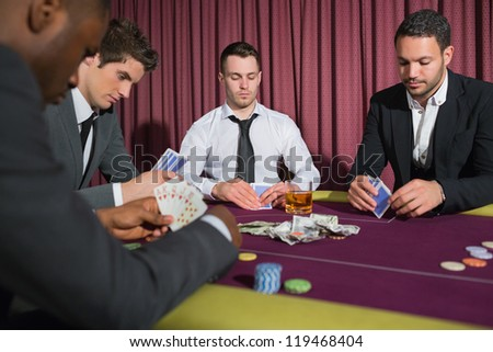 Men playing high stakes poker game in casino - stock photo
