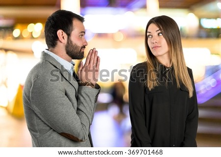 Men pleading at his girlfriend on unfocused background
