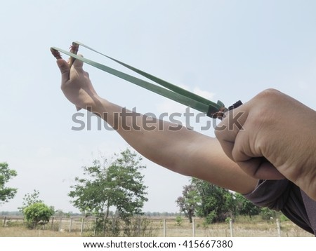 men pulling sling shot  - stock photo