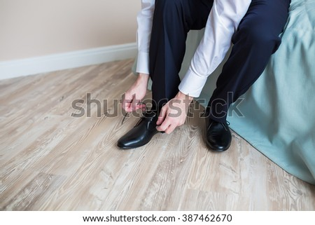 Men putting his black shoes. Hands of men getting ready in suit