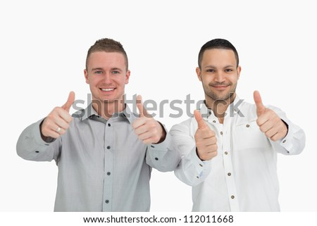Men putting their thumbs up against a white background - stock photo
