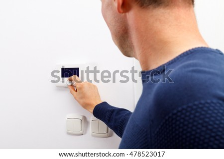 Men regulate temperature on control panel of central heating at wall in living room.