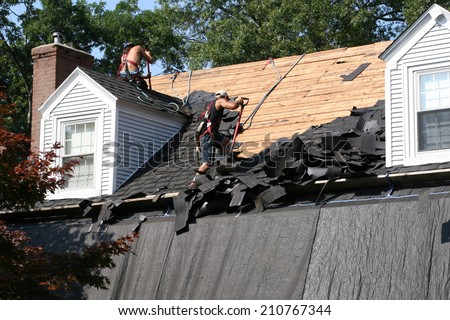 men removing roof shingles on home