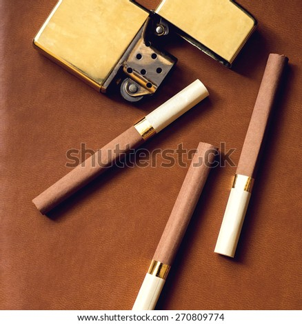 Men's accesory, golden lighter and cigarettes on a brown leather background.. - stock photo