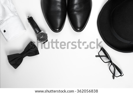 Men's accessories men's shoes, watches, glasses, bow tie, sleeve shirt and hat/Black and white minimalistic composition on a white background. Classic men's accessories. Top view