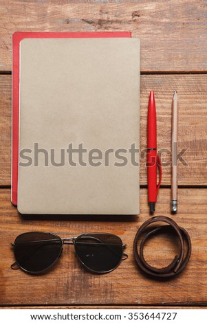 Men's accessories - sunglasses, notebooks, pens, belt on the wooden table