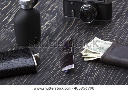 Men's accessories: wallet, flask, sunglasses, camera and perfume.