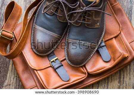 Men's accessories with brown leather bag and brown shoes on wooden background - stock photo