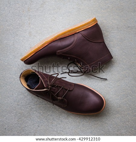 Men's accessories with brown leather boots on gray grunge background - stock photo