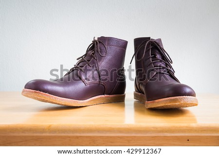 Men's accessories with brown leather boots on wooden table, bar or counter over gray wall background