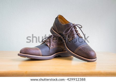 Men's accessories with brown leather shoes on wooden table, bar or counter over gray wall background - stock photo