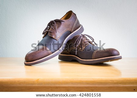 Men's accessories with brown leather shoes on wooden table, bar or counter over white wall background