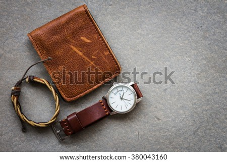 Men's accessories with brown leather wallet and watch on gray background - stock photo