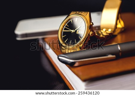 Men's accessory, golden watch, pen and mobile phone on the leather diary - stock photo