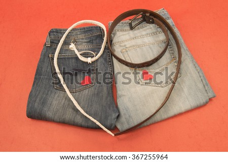 Men's and women's jeans, belts, heart, Valentine's day on red background. - stock photo