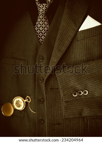 Men's black suit with golden pocket watch. Sepia image. - stock photo