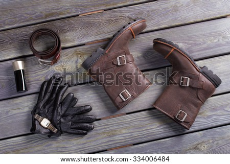 Men's boots and accessories on a wooden background. Stylish men's things. - stock photo