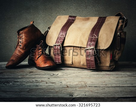 Men's boots and brown bag on wooden table over wall grunge background