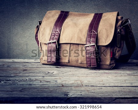 Men's brown bag on wooden table over wall grunge background - stock photo