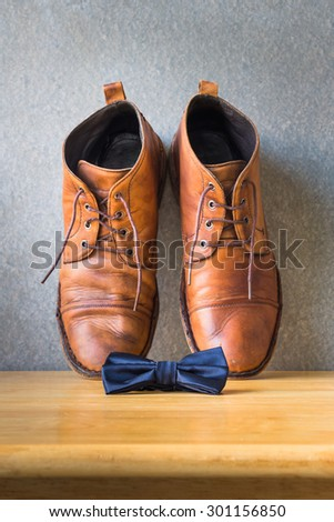 Men's casual, bow tie and boots on wooden over wall grunge background - stock photo