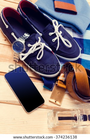 Men's casual clothes and accessories on wooden background