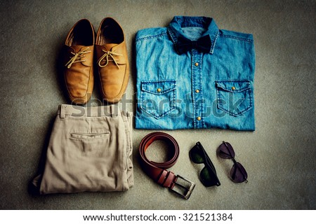 Men's casual outfits, jean shirt with bow tie, brown pants, sunglasses and shoes on gray background - stock photo