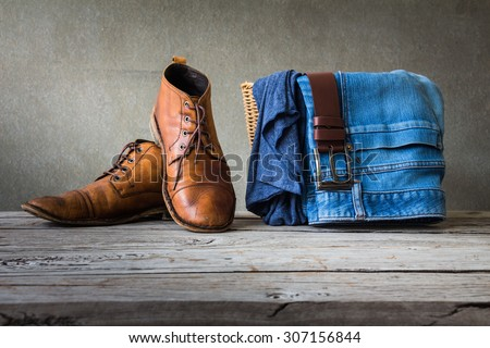 Men's casual outfits on wooden table over grunge background - stock photo