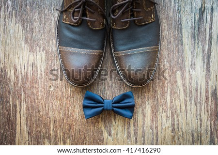 Men's casual outfits with brown shoes and blue bowtie on rustic wooden background - stock photo
